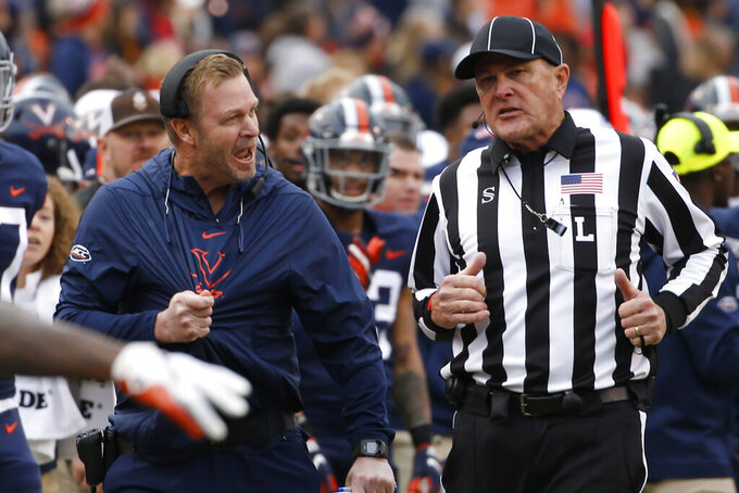 Virginia head coach Bronco Mendenhall, left, disputes a call during the second half of an NCAA college football game against Virginia Tech in Charlottesville, Va., Friday, Nov. 29, 2019. Virginia defeated Virginia Tech 39-30. (AP Photo/Steve Helber)