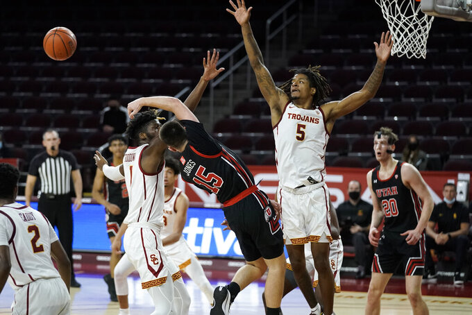 Utah's Rylan Jones, center, passes the ball as he is defended by Southern California's Isaiah White, right, and Chevez Goodwin during the first half of an NCAA college basketball game, Saturday, Jan. 2, 2021, in Los Angeles. (AP Photo/Jae C. Hong)
