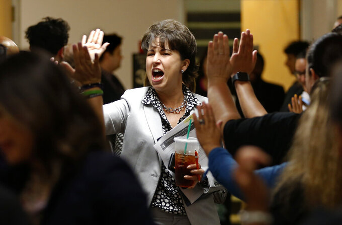 FILE — In this Feb. 13, 2019, state Sen. Connie Leyva, D-Chino, gets high-fives from supporters of a measure who packed the hallway of the Capitol in Sacramento, Calif. On Monday, Aug. 30, 2021, the California Legislature passed Leyva's bill SB331 that would prohibit secret agreements to settle harassment and discrimination cases in the workplace. California already bans secret agreements in cases involving sexual harassment and sex discrimination. This bill would extend the law to include other forms of harassment and discrimination, including race, religion and gender identity. (AP Photo/Rich Pedroncelli, File)