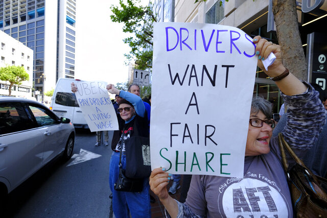 FILE - In this May 8, 2019, file photo Uber and Lyft drivers carry signs during a demonstration outside of Uber headquarters in San Francisco. A California law that makes it harder for companies to treat workers as independent contractors takes effect next week, forcing small businesses in and outside the state to rethink their staffing. (AP Photo/Eric Risberg, File)