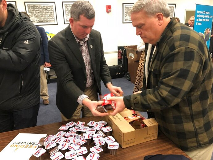 Kentucky Sen. President Robert Stivers, right, in the plaid sweater, works with state Rep. Matthew Koch on Monday, Jan. 13, 2020, in Frankfort, Ky., to help fill bags of food for schoolchildren at risk of hunger. Organizers said the goal was to distribute 2,100 bags of food to 18 schools or Head Start programs across Kentucky. (AP Photo/Bruce Schreiner)