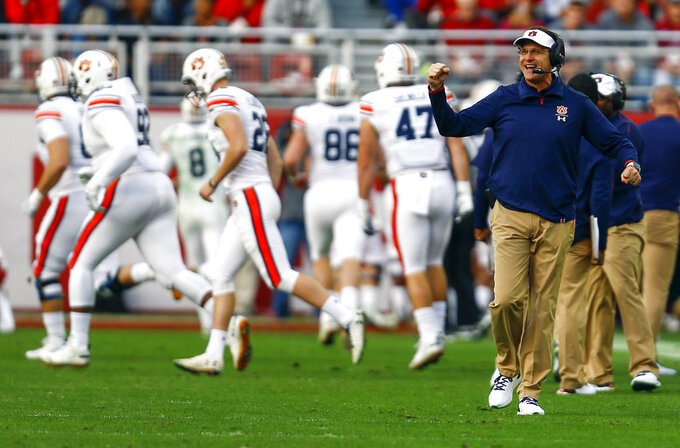 Auburn head coach Gus Malzahn, front right, reacts after his team scored a touchdown against Alabama during the first half of an NCAA college football game, Saturday, Nov. 24, 2018, in Tuscaloosa, Ala. (AP Photo/Butch Dill)