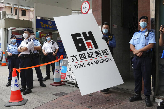 Police officers take away a cardboard from the June 4th Museum as an evidence, in Hong Kong. Thursday, Sept. 9, 2021. A dozen Hong Kong pro-democracy activists pleaded guilty on Thursday to participating and inciting others to take part in last year's unauthorized candlelight vigil to mark the bloody Tiananmen Square crackdown, amid an ongoing crackdown on dissent in Hong Kong which has seen dozens of activists arrested. (AP Photo/Kin Cheung)