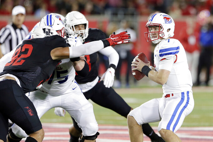 Houston defensive lineman Logan Hall (92) reaches out to get SMU quarterback Shane Buechele, right, for a sack during the first half of an NCAA college football game Thursday, Oct. 24, 2019, in Houston. (AP Photo/Michael Wyke)