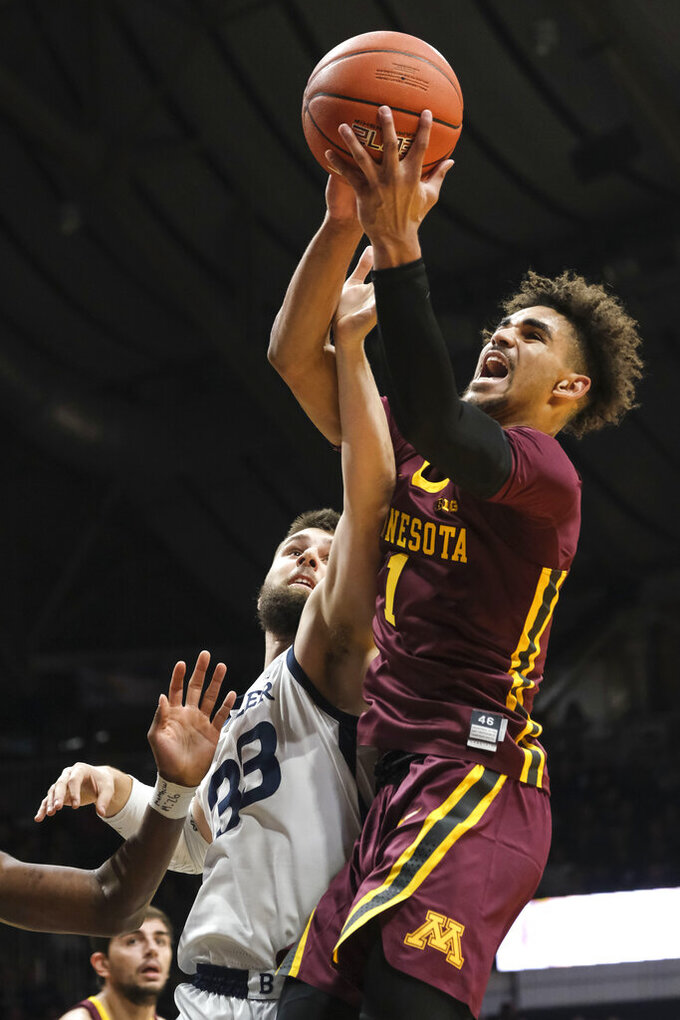 Minnesota guard Tre' Williams (1) battles for a rebound with Butler forward Bryce Golden (33) in the first half of an NCAA college basketball game in Indianapolis, Tuesday, Nov. 12, 2019. (AP Photo/AJ Mast)