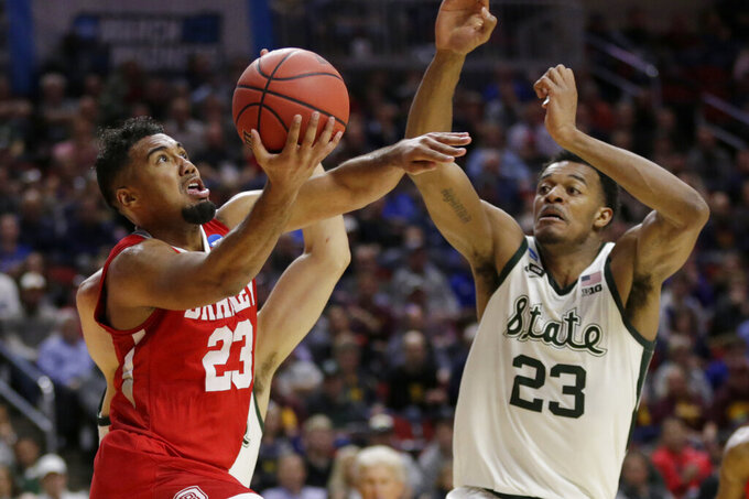 Bradley's Dwayne Lautier-Ogunleye (23) goes for a basket against Michigan State's Xavier Tillman, right, and Conner George, rear, during the first half of a first round men's college basketball game in the NCAA Tournament in Des Moines, Iowa, Thursday, March 21, 2019. (AP Photo/Nati Harnik)
