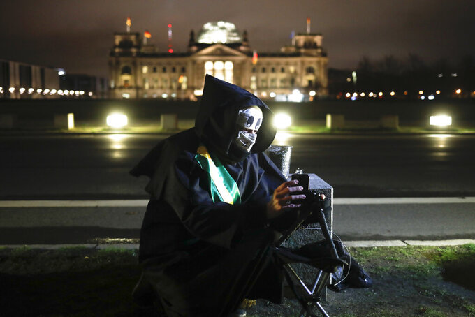 Brazilian activist and artist Rafael Puetter, dressed as the grim reaper, sits in front of the Reichstag and set up a live stream during a one-man protest through Berlin, Germany, early Wednesday, April 7, 2021. The multimedia artist starts his performance at the Brazilian embassy in Berlin at midnight every night to protest against Brazil's COVID-19 policies. Rafael Puetter walks to the Brandenburg Gate and then to the nearby German parliament building, in front of which he counts out a sunflower seed to represent each of the lives that were lost over the past 24 hours in Brazil because of the coronavirus pandemic. (AP Photo/Markus Schreiber)