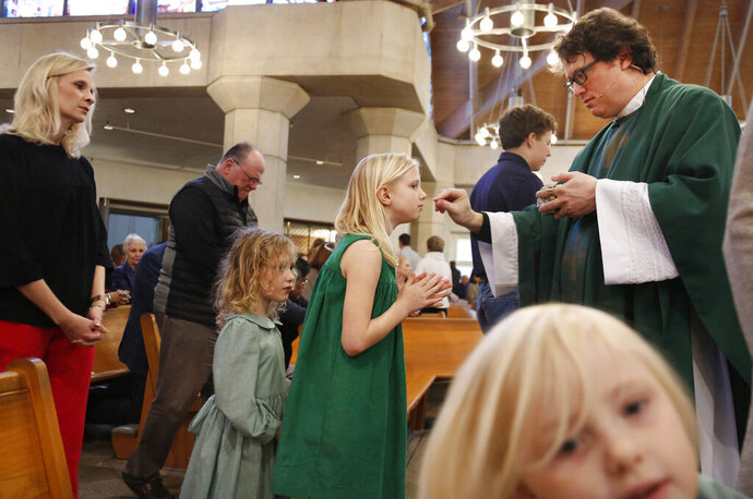 In this Feb. 9, 2020, photo, the Whitfield family, wife Alli, left, daughters Zoe-Catherine, 5, second from left, and Maggie, 9, second from right, receive communion from their dad and husband, The Rev. Joshua Whitfield, right, during Sunday Mass at St. Rita Catholic Community in Dallas. In 2009 the Whitfields, who were Episcopalian, converted to Catholicism. (AP Photo/Jessie Wardarski)