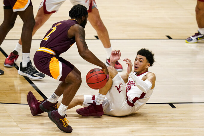 Iona guard Asante Gist (2) is fouled as he drives by Alabama guard Jahvon Quinerly (13) in the second half of a first-round game in the NCAA men's college basketball tournament at Hinkle Fieldhouse in Indianapolis, Saturday, March 20, 2021. (AP Photo/Michael Conroy)