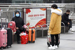 Travelers sit with their luggage outside the closed Hankou Railway Station in Wuhan in central China's Hubei Province, Thursday, Jan. 23, 2020. Overnight, Wuhan authorities announced that the airport and train stations would be closed, and all public transportation suspended by 10 a.m. Friday. Unless they had a special reason, the government said, residents should not leave Wuhan, the sprawling central Chinese city of 11 million that's the epicenter of an epidemic that has infected nearly 600 people. (Chinatopix via AP)