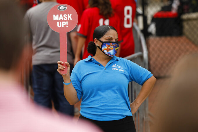 Security reminds fans to mask up before entering Sanford Stadium before the start of the Georgia-Tennessee NCAA college football game in Athens, Ga., on Saturday, Oct. 10, 2020. (Joshua L. Jones/Athens Banner-Herald via AP)