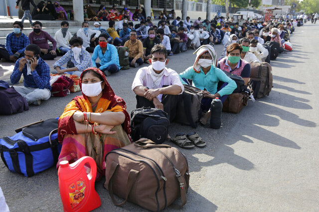 Migrant workers from other states trying to return to their homes wait for transportation to a train station in Ahmedabad, India, Sunday, May 17, 2020. Tens of thousands of migrant laborers have been returning from big cities to their villages after losing jobs because of a countrywide lockdown imposed in late March to contain the spread of the coronavirus. (AP Photo/Ajit Solanki)