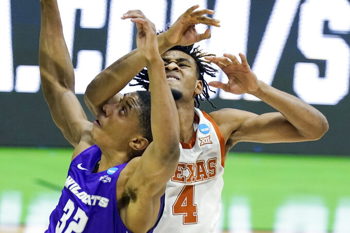 Abilene Christian's Joe Pleasant (32) and Texas' Greg Brown (4) battle for position under the basket during the first half of a college basketball game in the first round of the NCAA tournament at Lucas Oil Stadium in Indianapolis Saturday, March 20, 2021. (AP Photo/Mark Humphrey)