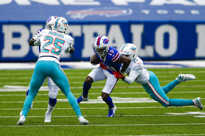 Buffalo Bills wide receiver Isaiah McKenzie (19) is tackled by Miami Dolphins free safety Eric Rowe (21) in the first half of an NFL football game, Sunday, Jan. 3, 2021, in Orchard Park, N.Y. (AP Photo/John Munson)