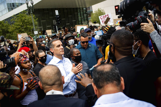 Los Angeles Mayor Eric Garcetti joins pastors and marchers outside LAPD Headquarters during a demonstration demanding justice for George Floyd, Tuesday, June 2, 2020 in Los Angeles, Floyd, a black man, died after being restrained by Minneapolis police officers on May 25.  (Sarah Reingewirtz/The Orange County Register via AP)