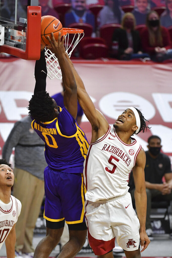LSU forward Mwani Wilkinson (0) is fouled as he tries to get past Arkansas guard Moses Moody (5) during the second half of an NCAA college basketball game in Fayetteville, Ark. Saturday, Feb. 27, 2021. (AP Photo/Michael Woods)