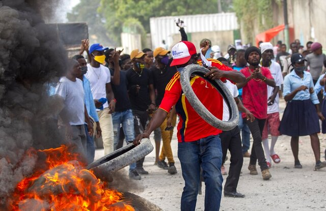 A protester adds tires to a burning barricade during a protest march to demand answers after the kidnapping and murder of high school senior Evelyne Sincère, in Port-au-Prince, Haiti, Thursday, Nov. 5, 2020. The young woman was found in a trash heap Sunday after relatives said they were unable to pay the large ransom demanded by her captors. Human rights groups contend the incident highlights the nation's worsening security crisis. (AP Photo/Dieu Nalio Chery)