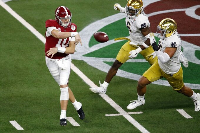 Alabama quarterback Mac Jones (10) throws a pass under pressure from Notre Dame linebacker Jeremiah Owusu-Koramoah (6) and defensive lineman Myron Tagovailoa-Amosa (95) in the second half of the Rose Bowl NCAA college football game in Arlington, Texas, Friday, Jan. 1, 2021. (AP Photo/Roger Steinman)
