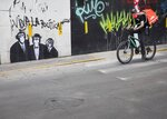 A piece of street art shows three chimps dressed in suits and a spray painted message that reads in Spanish:
