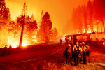 The Caldor Fire burns along both sides of Highway 50 as firefighters work to stop its eastward spread in Eldorado National Forest, Calif., on Thursday, Aug. 26, 2021. (AP Photo/Noah Berger)