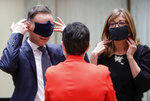 German Foreign Minister Heiko Maas, left, and Bulgaria's Foreign Minister Ekaterina Zharieva, right, put on their face masks, to prevent the spread of coronavirus, as they speak with Spain's Foreign Minister Arancha Gonzalez during an EU foreign ministers at the European Council building in Brussels, Monday, July 13, 2020. European Union foreign ministers meet for the first time face-to-face since the pandemic lockdown and will assess their discuss their relations with China and Turkey. (Stephanie Lecocq, Pool Photo via Ap)