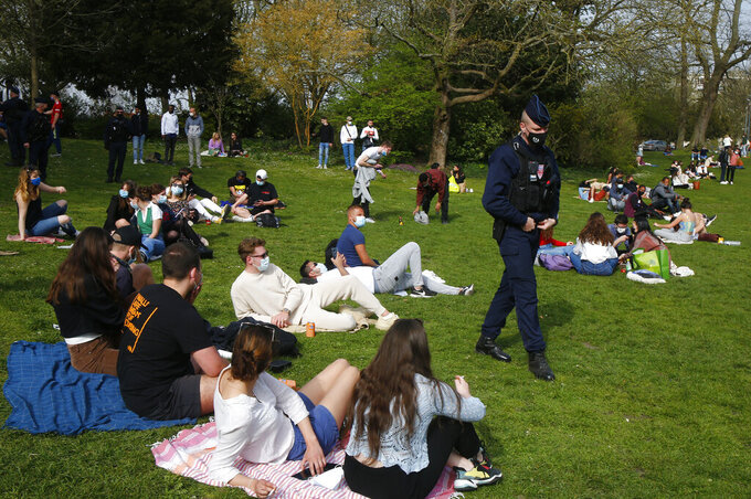 """A police officer patrols as people enjoy the sun in the Vauban park in Lille, northern France, Thursday, April 1, 2021. France's prime minister Jean Castex on Thursday defended new nationwide measures to combat a resurgent coronavirus in France that include closing schools for at least three weeks and putting in place a month-long domestic travel ban, the government has acted """"consistently and pragmatically.""""(AP Photo/Michel Spingler)"""