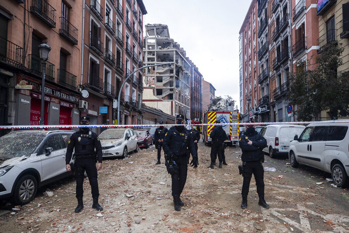 Police officers cordon off Toledo Street following an explosion in downtown Madrid, Spain, Wednesday, Jan. 20, 2021. A loud explosion has partially destroyed a small building flanked by a school and a nursing home in the center of Spain's capital. (AP Photo/Bernat Armangue)