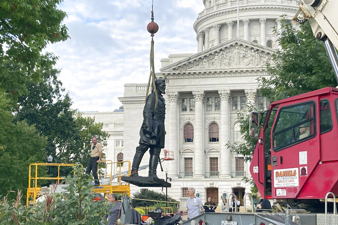 Workers reinstall a statue of Wisconsin abolitionist Col. Hans Christian Heg outside the state Capitol in Madison, Wis., on Tuesday, Sept. 21, 2021. Protesters tore the 9-foot-6-inch statue down and ripped its head off in June 2020 during a demonstration over George Floyd's death in Minneapolis. (AP Photo/Todd Richmond)