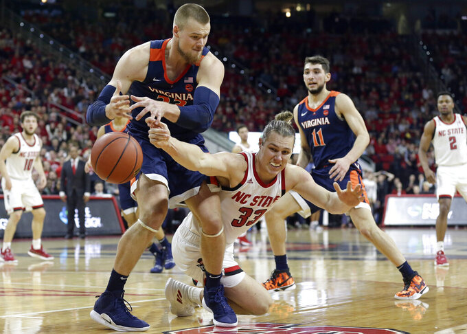 Virginia's Jack Salt, left, and North Carolina State's Wyatt Walker reach for a loose ball during the first half of an NCAA college basketball game in Raleigh, N.C., Tuesday, Jan. 29, 2019. (AP Photo/Gerry Broome)
