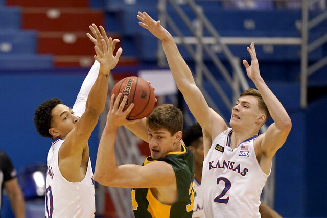 North Dakota State's Rocky Kreuser, center, is pressured by Kansas' Jalen Wilson, left and Christian Braun (2) during the first half of an NCAA college basketball game Saturday, Dec. 5, 2020, in Lawrence, Kan. (AP Photo/Charlie Riedel)