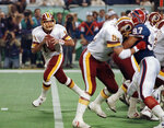 FILE - In this Jan. 26, 1992, file photo, Washington Redskins quarterback Mark Rypien, left, drops to pass during NFL football's Super Bowl XXVI in Minneapolis. Rypien has been arrested in Washington state on suspicion of domestic violence. The Spokesman-Review cites Spokane police saying Rypien was facing a charge of fourth-degree assault. Rypien, 56, was processed at the Spokane County Jail at around 6:30 p.m. Sunday and was awaiting a court appearance Monday, July 1, 2019. (AP Photo/Jim Mone, File)