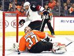 Arizona Coyotes' Phil Kessel, rear, scores a goal past Philadelphia Flyers goaltender Brian Elliott (37) during the first period of an NHL hockey game, Thursday, Dec. 5, 2019, in Philadelphia. (AP Photo/Derik Hamilton)