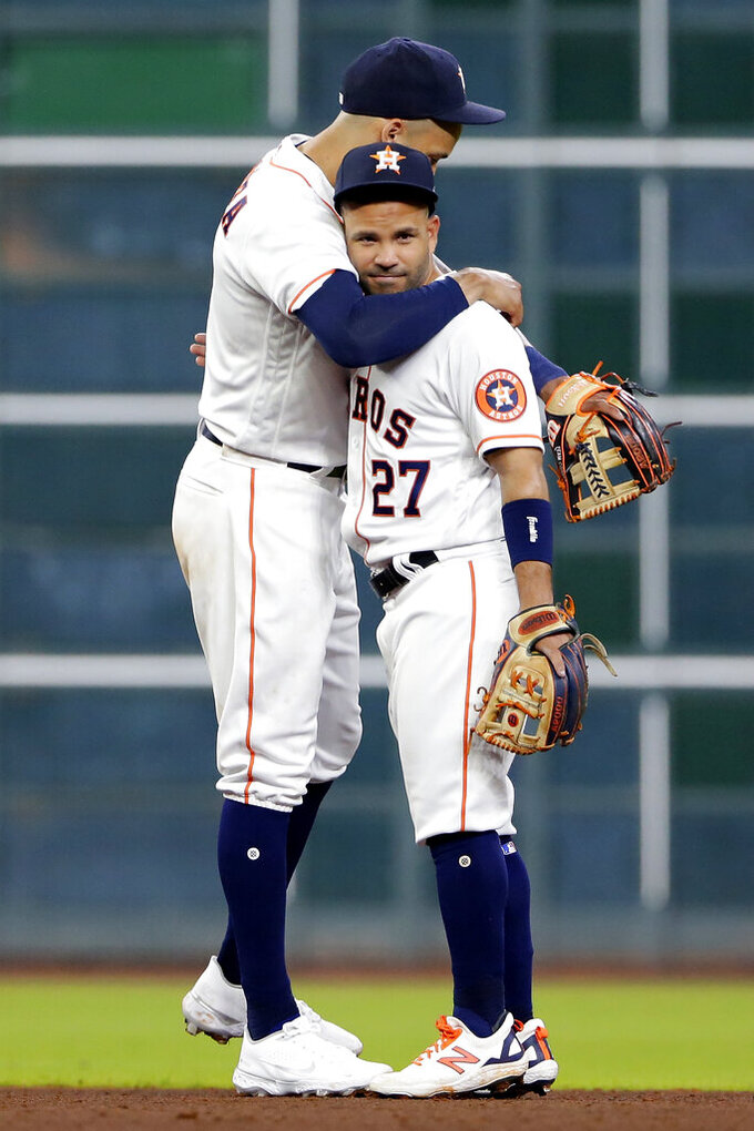 Houston Astros shortstop Carlos Correa, left, and second baseman Jose Altuve (27) hug after the team's 6-2 win over the Oakland Athletics in a baseball game Thursday, April 8, 2021, in Houston. (AP Photo/Michael Wyke)