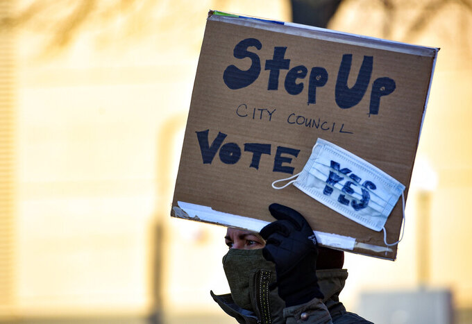 A demonstrator holds a sign demanding a mask mandate from the city council outside Carnegie Town Hall in Sioux Falls, S.D., Monday, Nov. 16, 2020. An increasing number of governors and mayors are imposing restrictions ahead of Thanksgiving for fear that holiday travel and family gatherings will only worsen the record-breaking, coast-to-coast resurgence of the coronavirus. (Erin Bormett/The Argus Leader via AP)