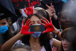 A woman takes a picture during a demonstration in Paris, France, Saturday, June 6, 2020, when protesting against the recent killing of George Floyd, a black man who died in police custody in Minneapolis, U.S.A., after being restrained by police officers on May 25, 2020. Further protests are planned over the weekend in European cities, some defying restrictions imposed by authorities because of the coronavirus pandemic. (AP Photo/Francois Mori)