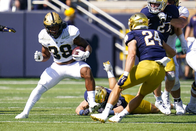 Purdue running back Dylan Downing (38) cuts aways from Notre Dame linebacker Jack Kiser (24) during the first half of an NCAA college football game in South Bend, Ind., Saturday, Sept. 18, 2021. (AP Photo/Michael Conroy)