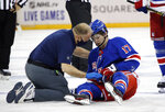Trainer Jim Ramsay tends to New York Rangers' Kevin Rooney following his collision with New York Islanders' Ross Johnston during the third period of an NHL hockey game Thursday, Jan. 14, 2021, in New York. (Bruce Bennett/Pool Photo via AP)