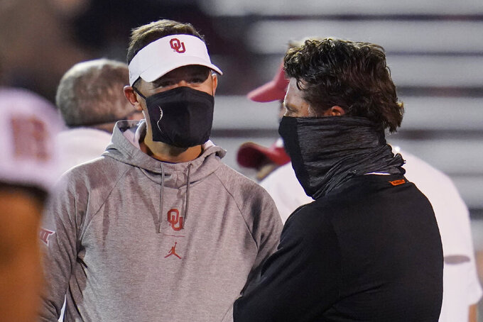 Oklahoma coach Lincoln Riley, left, talks with Oklahoma State coach Mike Gundy before an NCAA college football game in Norman, Okla., Saturday, Nov. 21, 2020. (AP Photo/Sue Ogrocki)