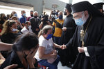 Greek Orthodox Metropolitan of the Archdiocese of Beirut, Elias Audi, gives condolences to families of four nurses of the Saint George Hospital University Medical Center who died in the Tuesday explosion at the seaport of Beirut, during a mass in Beirut, Lebanon, Thursday, Aug. 6, 2020. Visiting French president warned that without serious reforms the country would
