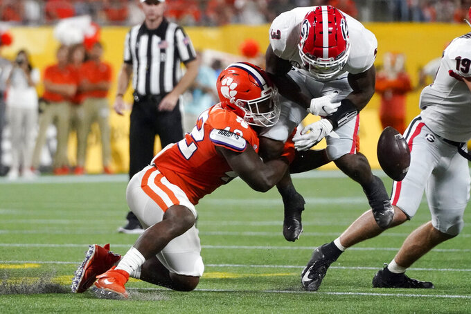 Clemson linebacker LaVonta Bentley, left, forces a fumble by Georgia running back Zamir White during the first half of an NCAA college football game Saturday, Sept. 4, 2021, in Charlotte, N.C. White recovered his own fumble. (AP Photo/Chris Carlson)