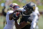 Wake Forest wide receiver Scotty Washington, right, catches a 31-yard touchdown pass against Elon defensive back Daniel Reid-Bennett in the second half of an NCAA college football game in Winston-Salem, N.C., Saturday, Sept. 21, 2019. Wake Forest won 49-7. (AP Photo/Nell Redmond)