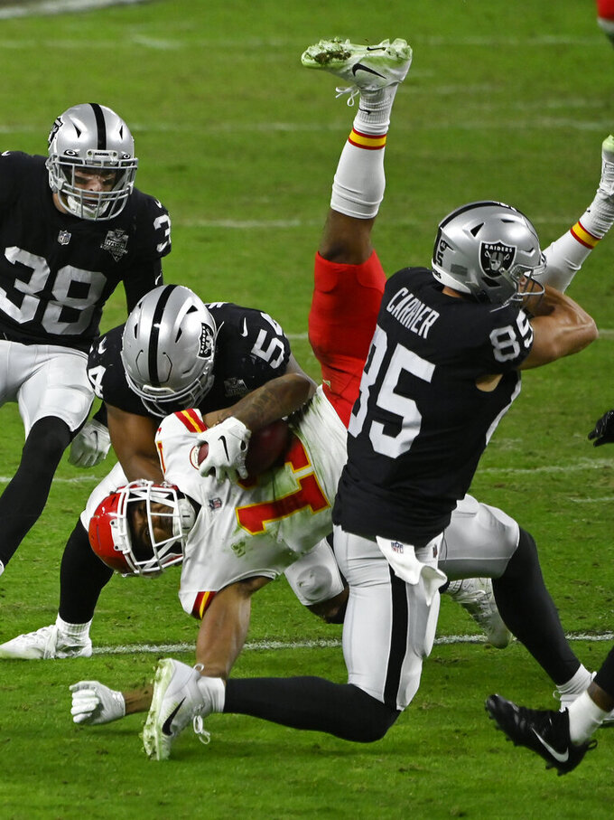 Kansas City Chiefs wide receiver Demarcus Robinson (11) is tackled by Las Vegas Raiders middle linebacker Raekwon McMillan (54) and tight end Derek Carrier (85) during the second half of an NFL football game, Sunday, Nov. 22, 2020, in Las Vegas. (AP Photo/David Becker)