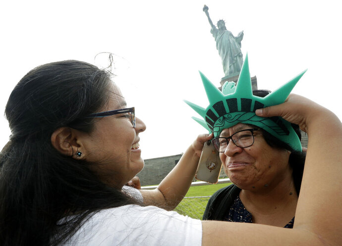 Karen Mejia, left, fits her mother Leonor Chipayo, with a souvenir Statue of Liberty foam visor while visiting the Statue of Liberty, Wednesday, Aug. 14, 2019, in New York. Both women are from Lima, Peru. Long before a Trump administration official suggested the poem inscribed on the Statue of Liberty welcomed only people from Europe, the words captured America's promise to newcomers at a time when the nation was also seeking to exclude many immigrants from landing on its shores.  (AP Photo/Kathy Willens)