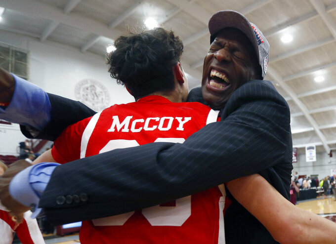Boston University's  Javante McCoy celebrates with head coach Joe Jones after winning the NCAA Patriot League Conference basketball championship over Colgate at Cotterell Court, Wednesday, March 11, 2020, in Hamilton, N.Y. (AP Photo/John Munson)