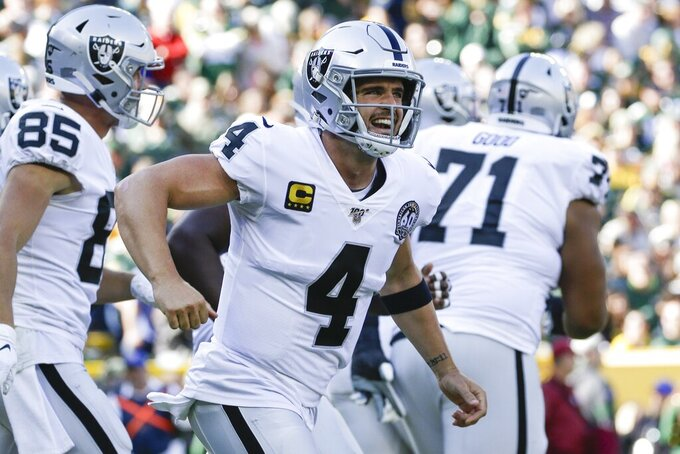 Oakland Raiders' Derek Carr celebrates after throwing a touchdown pass during the first half of an NFL football game against the Green Bay Packers Sunday, Oct. 20, 2019, in Green Bay, Wis. (AP Photo/Jeffrey Phelps)