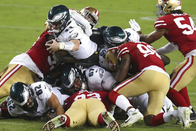 Philadelphia Eagles quarterback Carson Wentz, center left, dives forward for a first down during the second half of an NFL football game against the San Francisco 49ers in Santa Clara, Calif., Sunday, Oct. 4, 2020. (AP Photo/Jed Jacobsohn)
