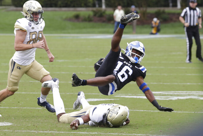 Duke safety Jaylen Stinson (16) gets upended by Georgia Tech place kicker Gavin Stewart (88) and Georgia Tech defensive back Myles Sims (16) as he returns a kickoff during the first half of an NCAA college football game in Durham, N.C., Saturday, Oct. 9, 2021. (AP Photo/Chris Seward)