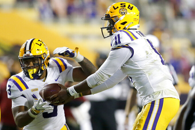 LSU quarterback TJ Finley (11) hands off the ball to running back Tyrion Davis-Price (3) during the first half of an NCAA college football game against South Carolina in Baton Rouge, La., Saturday, Oct. 24, 2020. (AP Photo/Brett Duke)