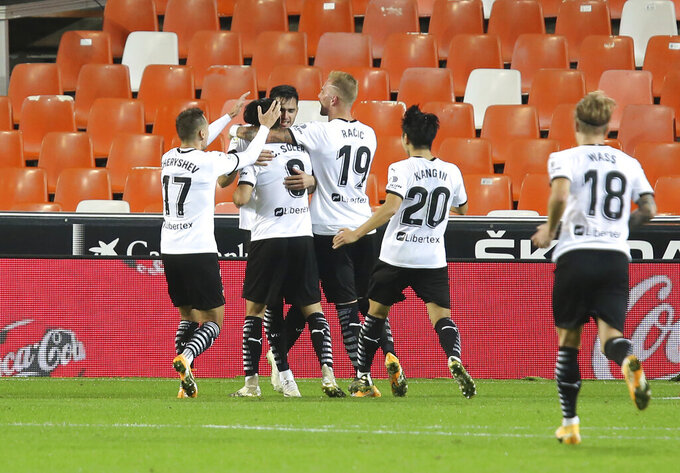 Valencia's team players celebrate after Carlos Soler scores his side's first goal during the Spanish La Liga soccer match between Valencia and Real Madrid at the Mestalla Stadium in Valencia, Spain, Sunday, Nov. 8, 2020. (AP Photo/Alberto Saiz)