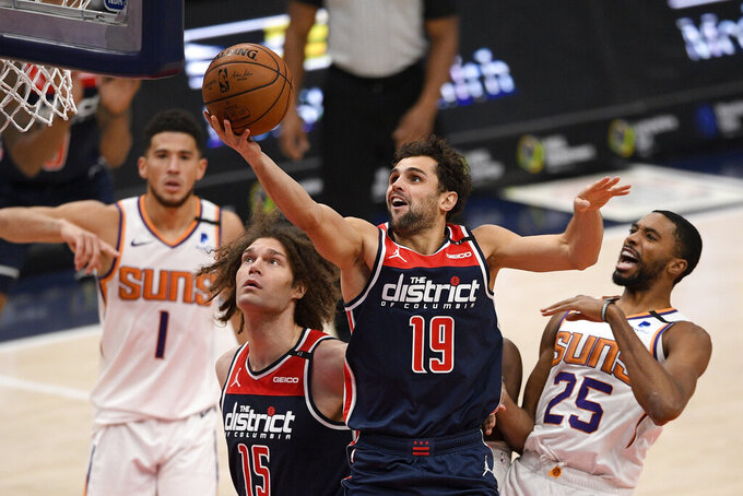 Washington Wizards guard Raul Neto (19) goes to the basket past Phoenix Suns forward Mikal Bridges (25) and guard Devin Booker (1) during the second half of an NBA basketball game, Monday, Jan. 11, 2021, in Washington. Wizards center Robin Lopez (15) looks on. (AP Photo/Nick Wass)